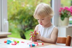 Toddler girl making cookies from plasticine Royalty Free Stock Photo