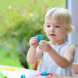 Toddler girl making cookies from plasticine Royalty Free Stock Photography