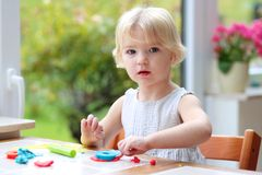 Toddler girl making cookies from plasticine Stock Images