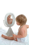 Toddler Girl in Mirror. Toddler girl sitting on floor, in front of wicker mirror, in white diaper cover, with string of pearls, on white background Stock Photography