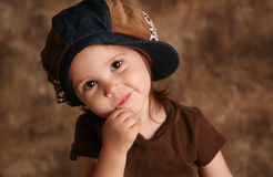 Toddler girl modeling. Portrait of an adorable toddler girl modeling a brown and blue jean denim hat posing for the camera Royalty Free Stock Photo