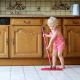 Toddler girl mopping kitchen floor Royalty Free Stock Photography