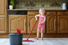 Toddler girl mopping kitchen floor royalty free stock photo