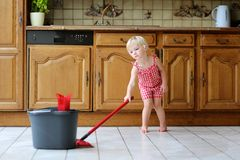 Toddler girl mopping kitchen floor Stock Photos