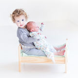 Toddler girl with newborn baby brother in toy bed Stock Image