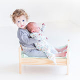 Toddler girl with newborn baby brother in toy bed Royalty Free Stock Images