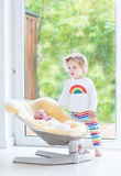 Toddler girl with newborn brother relaxing in swing Royalty Free Stock Images