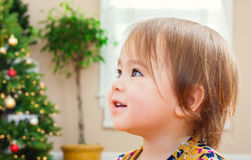 Toddler girl with a nice smile in front of her Christmas tree Stock Photos