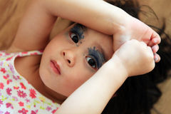 Toddler girl painted makeup her eyes with colored Stock Image