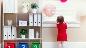 Toddler girl peeking out the window. Toddler girl peeking out of the window in her house Royalty Free Stock Images