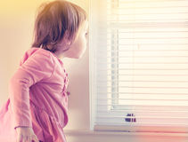 Toddler girl peeking out of the window. In her house Royalty Free Stock Image