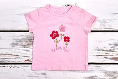Toddler girl pink cartoon t-shirt. Baby-girl casual pink t-shirt on white wooden background royalty free stock photo