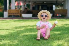 Toddler girl in pink summer overalls, hat and pink sunglasses sits on a green grass with ice cream in her hand and. Happy toddler girl in pink summer overalls royalty free stock photography