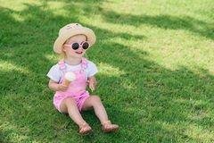 Toddler girl in pink summer overalls, hat and pink sunglasses sits on a green grass with ice cream in her hand and. Happy toddler girl in pink summer overalls royalty free stock image