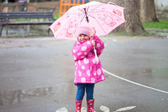 Toddler girl with pink umbrella Stock Images
