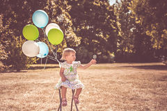 Toddler girl playing with balloons and bubbles Stock Image