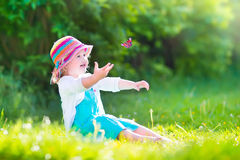 Toddler girl playing with butterfly stock images