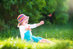 Toddler girl playing with butterfly Royalty Free Stock Photography