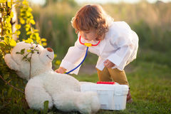 Toddler girl playing doctor with teddy bear putdoors Royalty Free Stock Photography