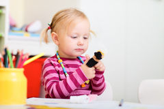 Toddler girl playing with finger puppets Stock Photo