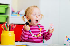 Toddler girl playing with finger puppets Royalty Free Stock Image