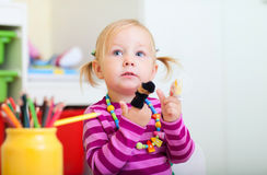 Toddler girl playing with finger toys Stock Photos