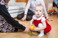 Toddler girl playing on floor of room with parents sitting near Stock Image