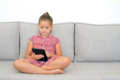 Toddler girl playing games on her tablet Stock Photography
