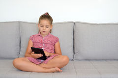 Toddler girl playing games on her tablet Royalty Free Stock Photography