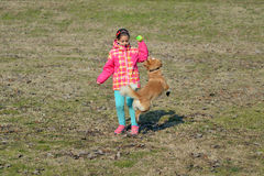 Toddler girl playing with her dog Royalty Free Stock Image