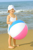 Toddler girl playing with her inflatable ball at beach Stock Photography