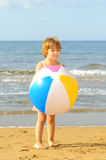 Toddler girl playing with her inflatable ball at beach Stock Photo