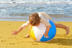 Toddler girl playing with her inflatable ball at beach Stock Images