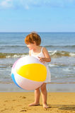 Toddler girl playing with her inflatable ball at beach Stock Image