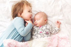 Toddler girl playing with her newborn sister Royalty Free Stock Photos