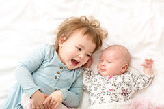 Toddler girl playing with her newborn sister Royalty Free Stock Photography