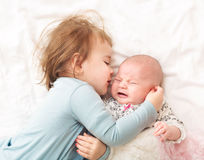 Toddler girl playing with her newborn sister Stock Photos