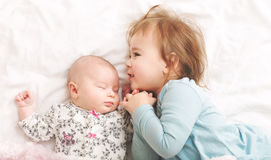 Toddler girl playing with her newborn sister Stock Images