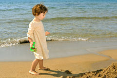 Toddler girl playing with her toys at a beach Stock Images