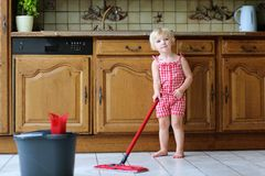 Toddler girl playing indoors mopping kitchen floor Royalty Free Stock Photography