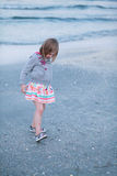 Toddler girl playing in mud, on the beach. Stock Photo