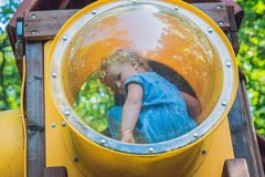 Toddler girl playing on multi-colored playground. A Toddler girl playing on multi-colored playground Royalty Free Stock Photos
