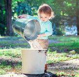 Toddler girl playing outside with buckets Stock Images