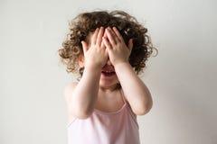 Toddler girl playing peekaboo Stock Photos