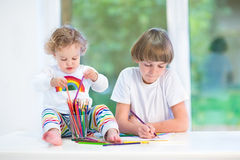 Toddler girl playing with pencils with her brother Royalty Free Stock Photo