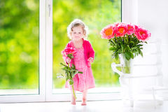 Toddler girl playing with peony flowers Stock Images