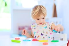 Toddler girl playing with plasticine indoors Royalty Free Stock Photo