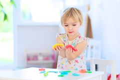Toddler girl playing with plasticine indoors Royalty Free Stock Photography