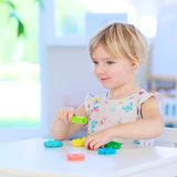 Toddler girl playing with plasticine indoors Royalty Free Stock Images