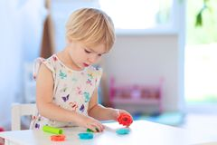 Toddler girl playing with plasticine indoors Royalty Free Stock Image